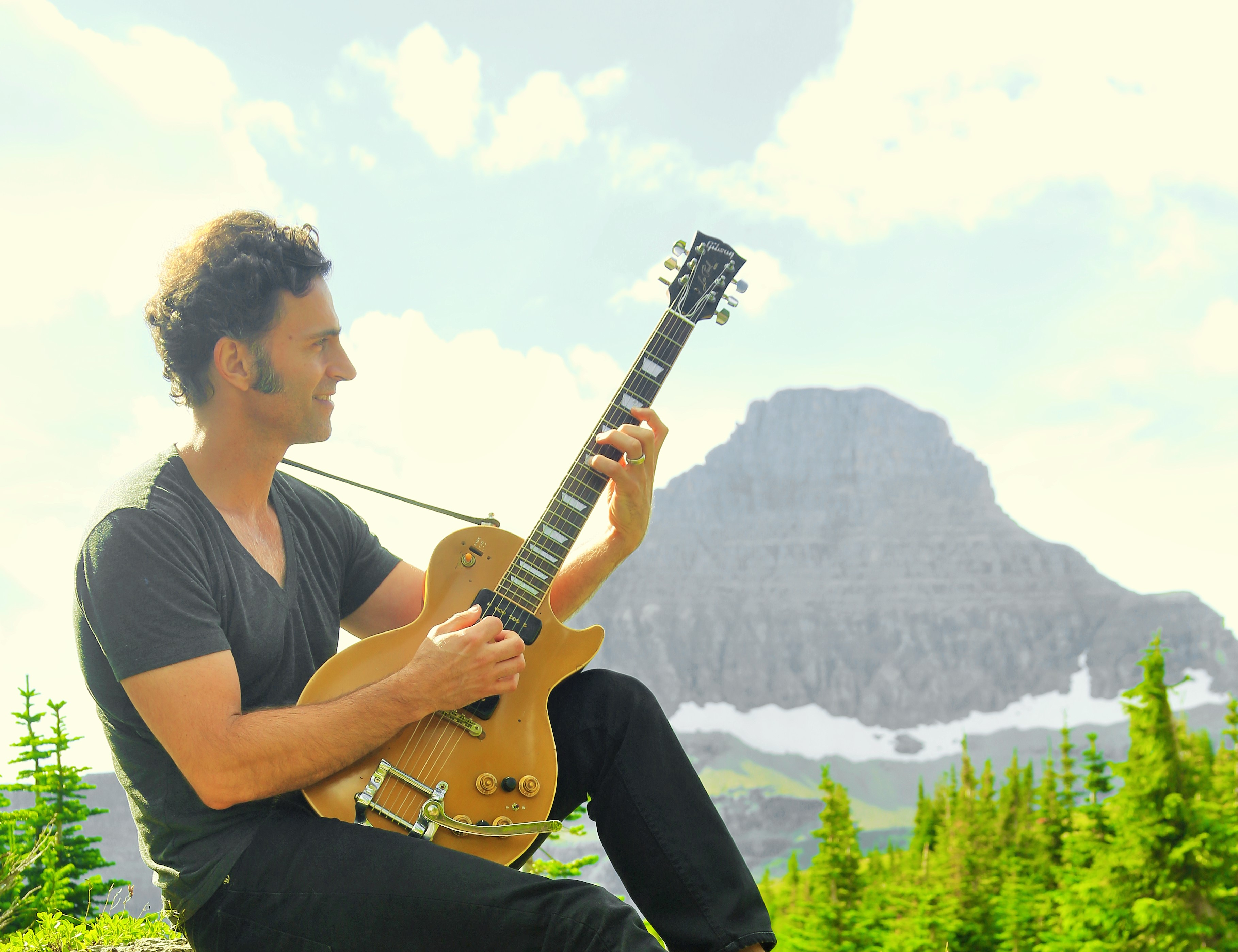 Dweezil Zappa playing a guitar out in nature