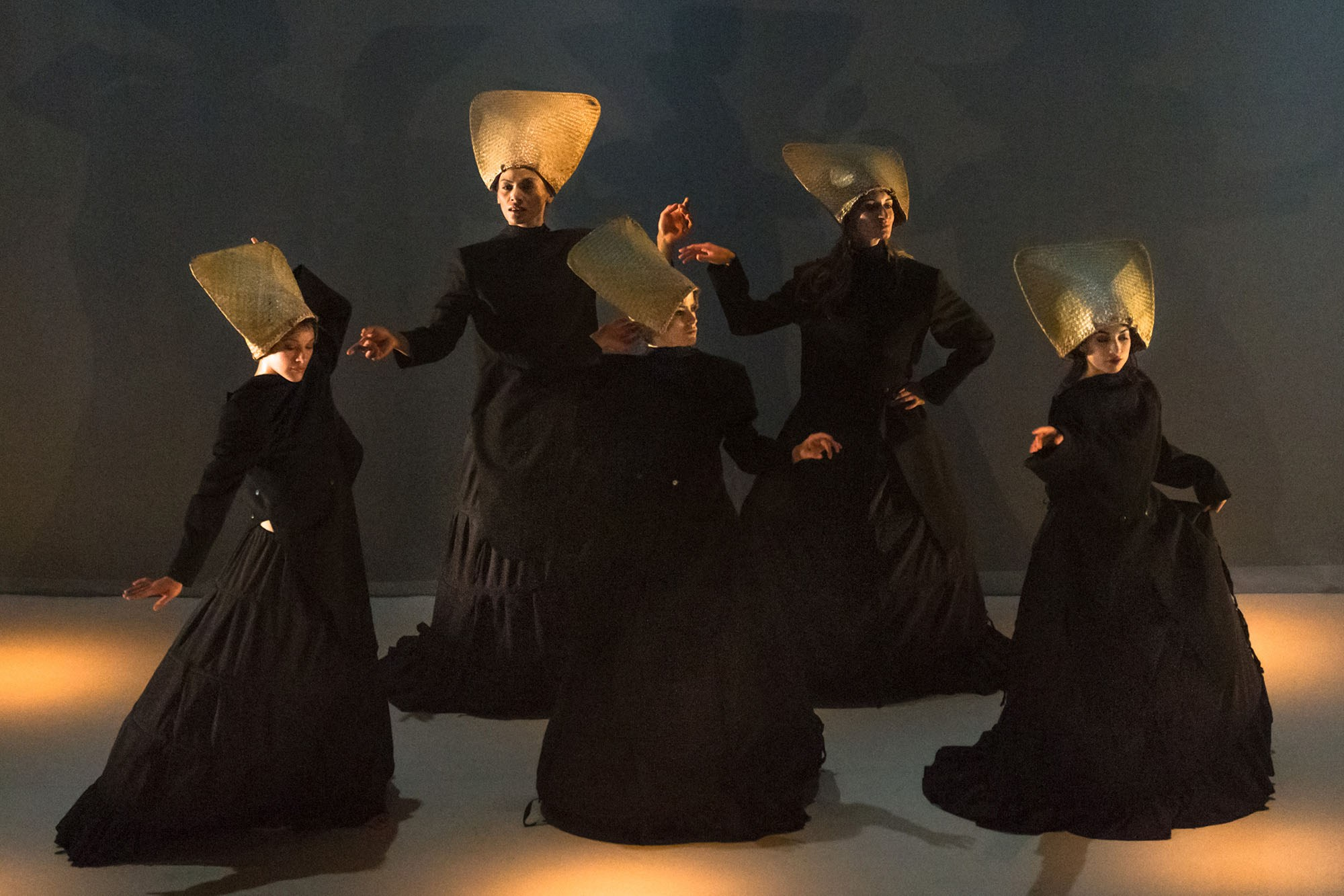 The five women dancers of Maha Wahine performing on stage in long black dresses and stylized headpieces