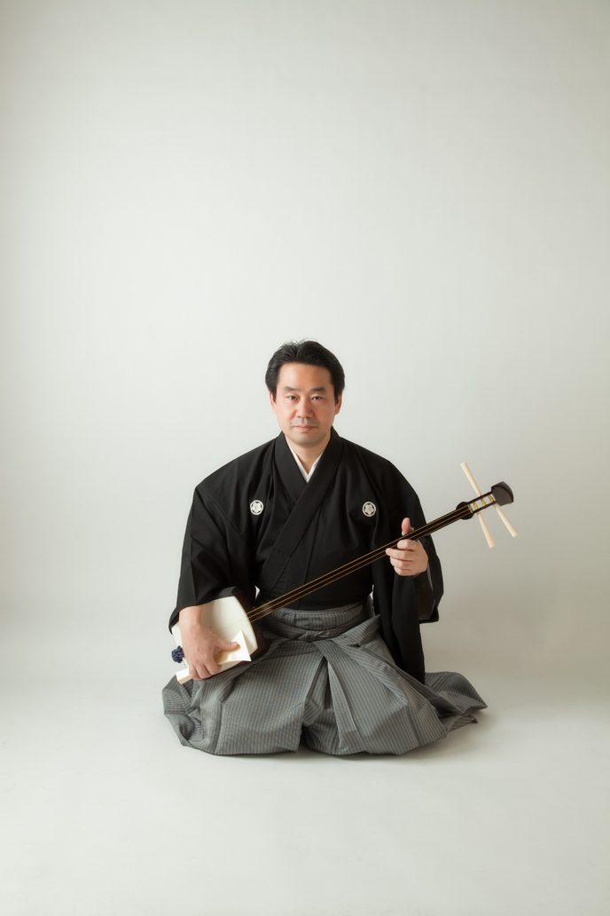 Shamisen Master Goshiro Kineya posing with his instrument