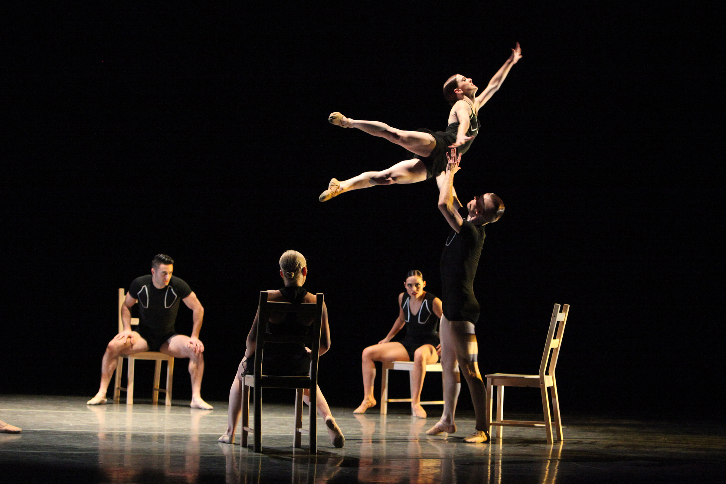Members Giordano Dance Chicago performing on stage, with one man lifting a woman over his head
